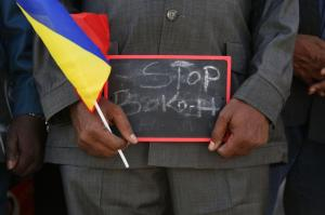 "A man holds a sign that reads ""Stop Boko Haram"" at a rally to support Chadian troops heading to Cameroon to fight Boko Haram in Ndjamena"