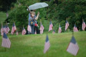 Oz Knarr, of Cincinnati, holds his toy musket as he passes miniature American flags placed at the graves of soldiers who died in the Civil War, Monday, May 25, 2015, at Spring Grove Cemetery in Cincinnati. The cemetery holds a Memorial Day service which includes Civil War reenactors and a 21-gun salute. (AP Photo/John Minchillo)