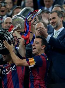 Spain's King Felipe VI, right, applauds as Barcelona's Xavi Hernandez lift the cup after winning the final of the Copa del Rey soccer match 3-1against Athletic Bilbao at the Camp Nou stadium in Barcelona, Spain, Saturday, May 30, 2015. (AP Photo/Emilio Morenatti)