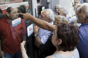 Pensioners waiting outside a closed National Bank branch and hoping to get their pensions, argue with a bank employee (L) in Iraklio on the island of Crete, Greece June 29, 2015. REUTERS/Stefanos Rapanis